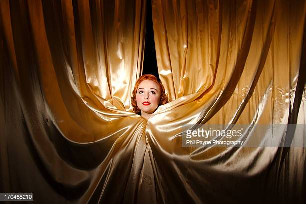 Red haired woman peeking out of curtains