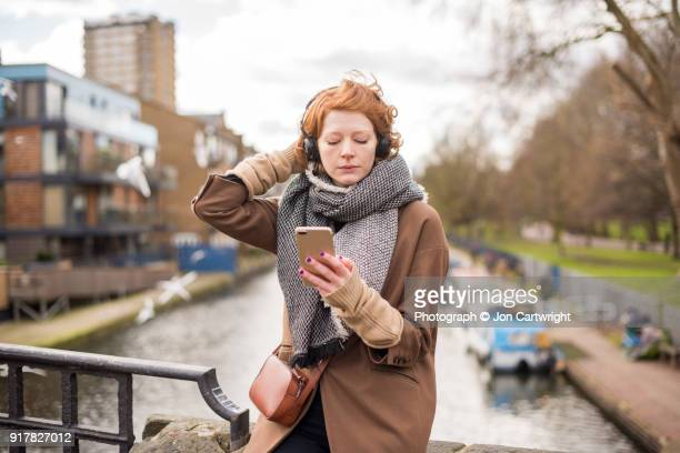 red haired woman sits on an east london canal bridge listening to music and using her smart phone - east london stock pictures, royalty-free photos & images