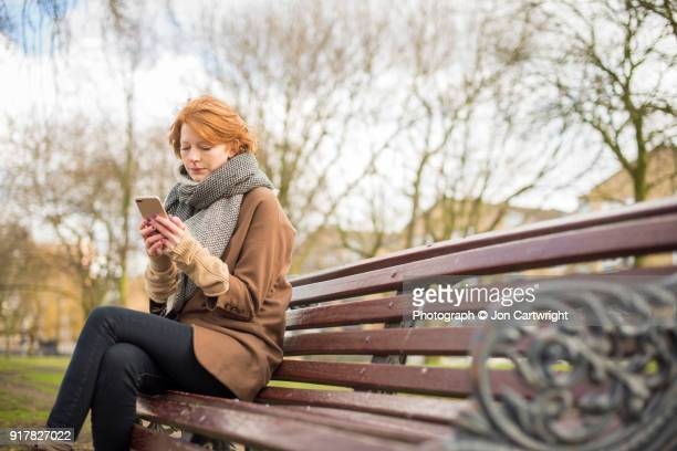 Red haired woman sitting on a bench using her smart phone
