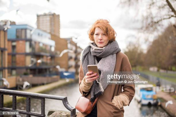 Red haired woman sitting on a bridge, using her smart phone