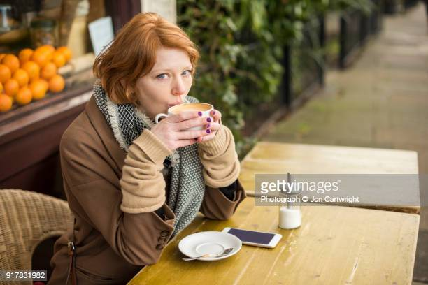 Red haired woman sitting outside a coffee shop on a cold day