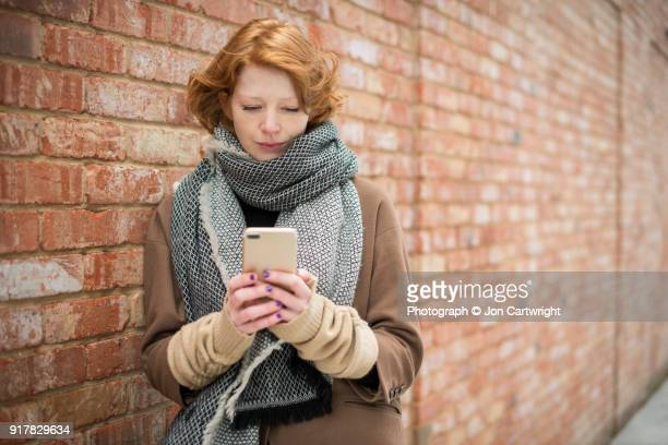 Red haired woman standing against a brick wall using her smart phone