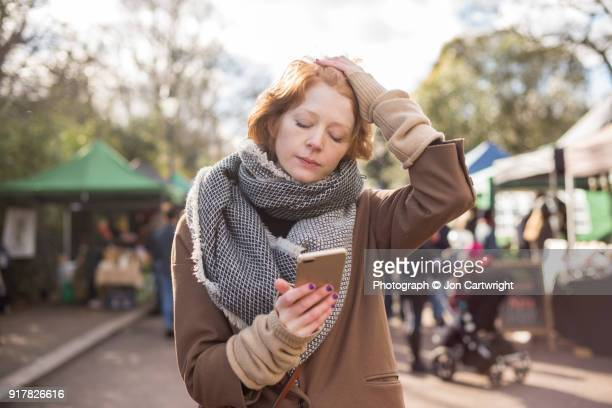 Red haired woman standing in a London markets looks at her smartphone with her hand on her head