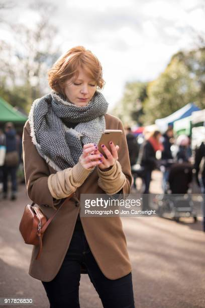 Red haired woman standing in a London markets using her smart phone