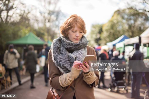 Red haired woman standing in a London markets using her smartphone