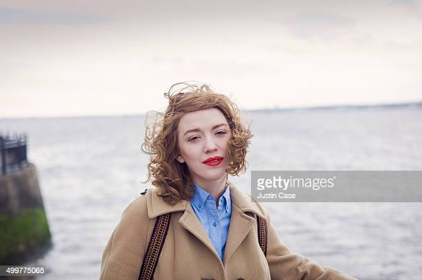 red haired woman standing in front of the sea