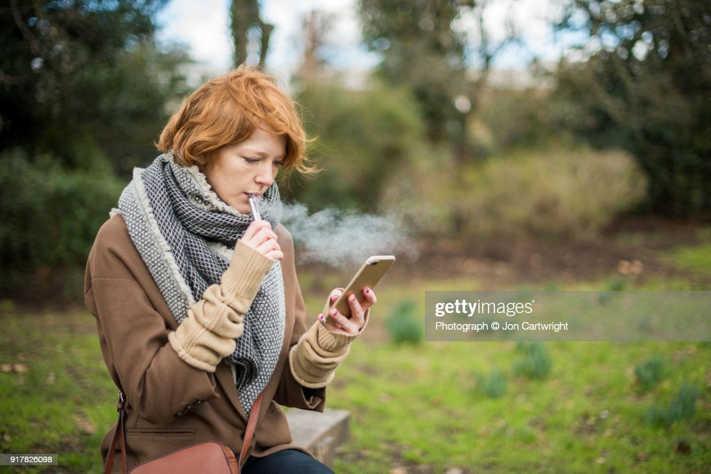 Red haired woman using an electronic cigarette and a smart phone in the countryside : Stock Photo