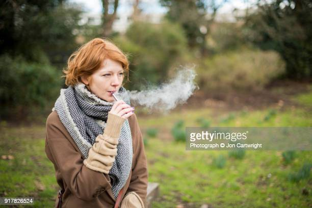 Red haired woman using an electronic cigarette in the countryside