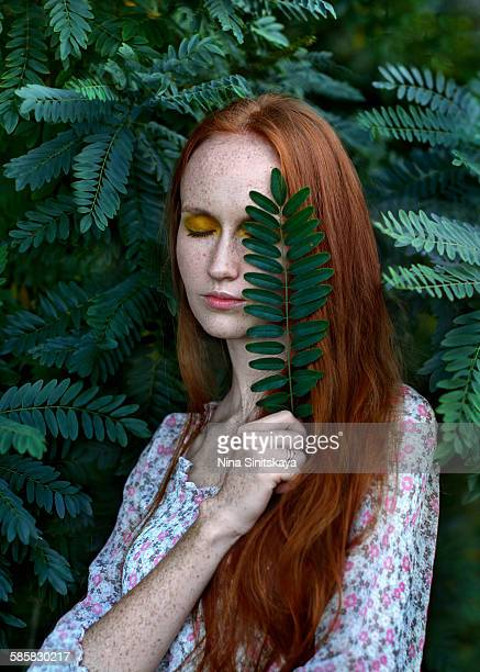 Red haired young woman with eyes closed in nature