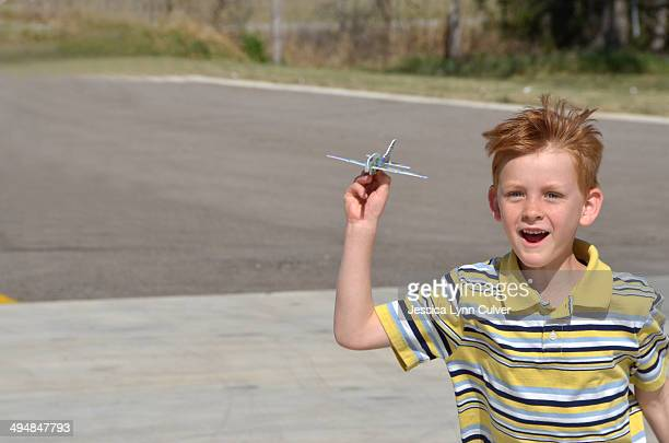 Red head boy running with a paper airplane glider.