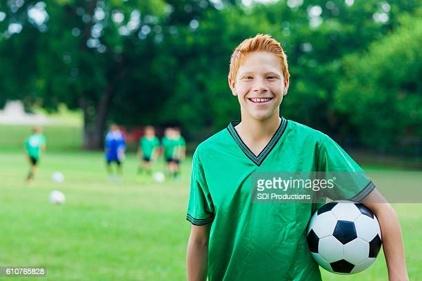 Red headed athlete with soccer ball