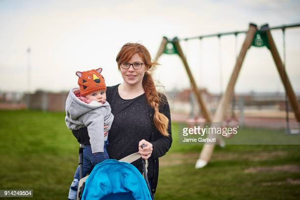 red headed british female carrying her child in a park - britain playgrounds stock pictures, royalty-free photos & images