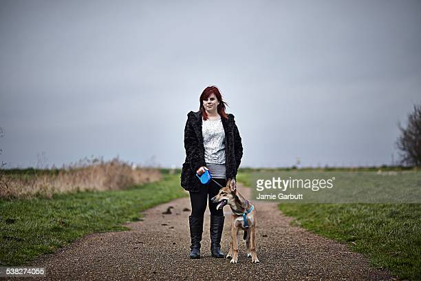 a red headed late teenage girl walking her dog - 馬具 ストックフォトと画像