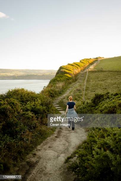 red headed woman walking along path between whitby and robinshoo - national park stock pictures, royalty-free photos & images