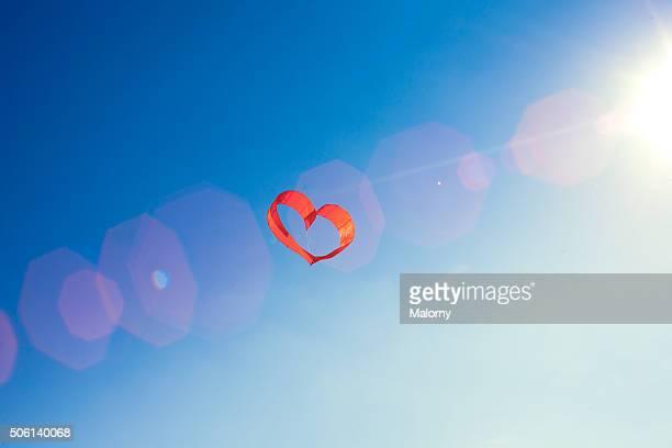 red heart and blue sky. love is in the air. - stimmungsvoller himmel stock-fotos und bilder