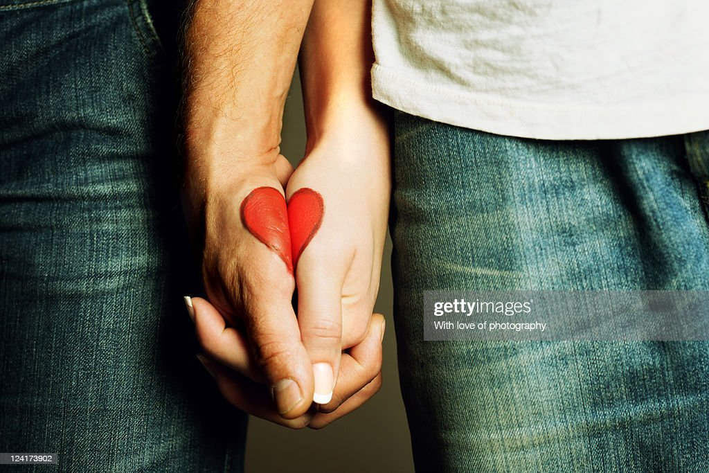 Red heart drawing on hands of couple : Stockfoto