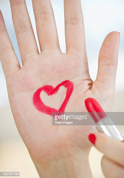 Red heart drawn on hand with lipstick
