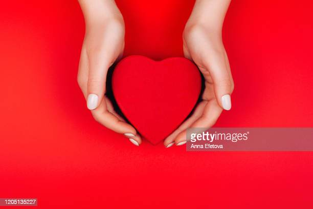 red heart gift box in woman hands - charity benefit stock pictures, royalty-free photos & images