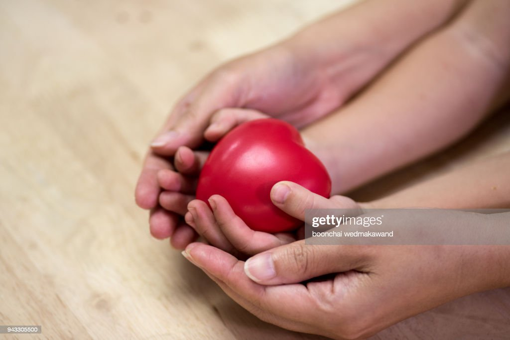 Red heart in child kid and mother hands on wooden table. : Stock Photo