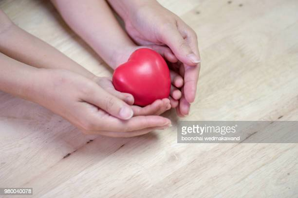 red heart in child kid and mother hands on wooden table. - organ donation stock photos and pictures