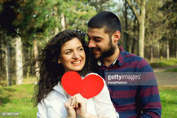 Red heart in hands of beautiful young couple