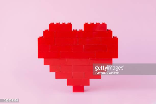 red heart made of toy building bricks, viewed from the front, on pink background. - coeur photos et images de collection