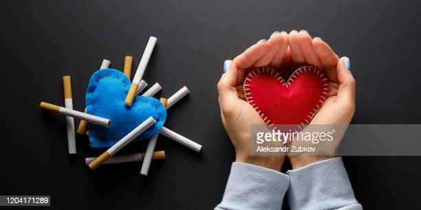 red heart or valentine in the hands of a girl, on a black background. nearby, cigarettes lie on a blue decorative heart. smoking destroys health. social problem. - endopack stock pictures, royalty-free photos & images