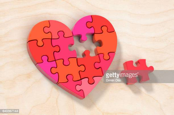 Red heart shape jigsaw puzzle, one piece aside