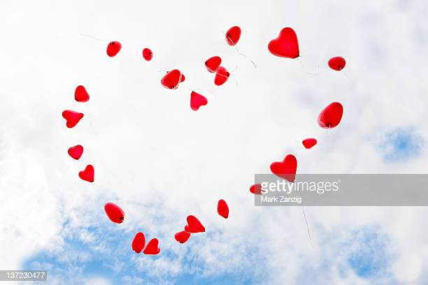 Red heart shaped balloons  in sky
