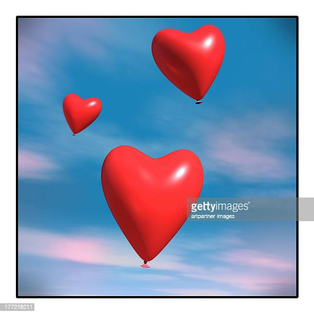 Red heart shaped balloons in the blue sky