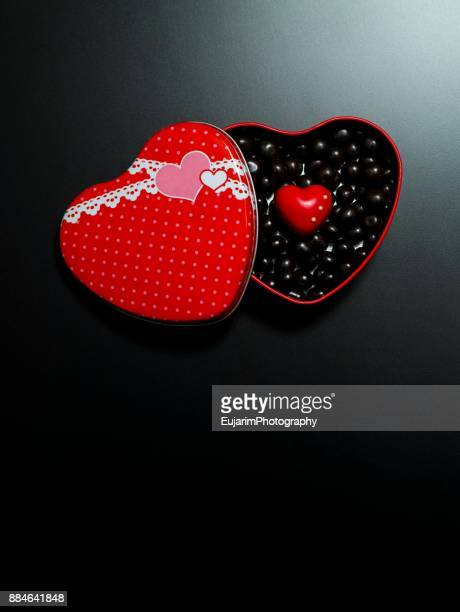 Red heart shaped box full of chocolate
