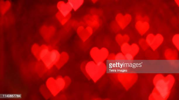 red heart shaped lens flares - heart background stock pictures, royalty-free photos & images