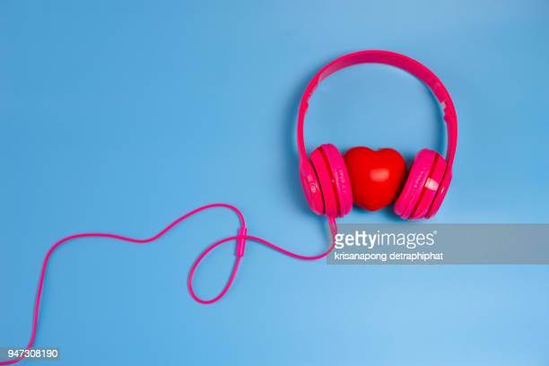red heart with headphones on blue background - objet rouge photos et images de collection