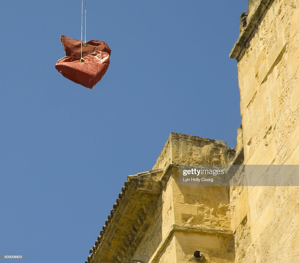 Red hearts hanging on wires by stone building : Stock Photo