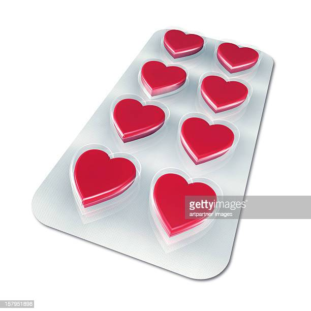 Red hearts in a blister pack on a white