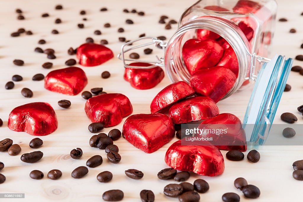 Red hearts in a glass jar and coffee beans : Stock Photo