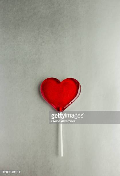 red heart-shaped lollipop on a colored plain background - lollipop stock pictures, royalty-free photos & images