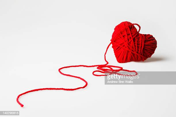 Red heart-shaped wool ball unraveling