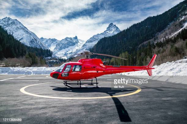 red helicopter in the mountains - helicopter photos stock pictures, royalty-free photos & images