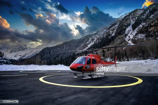 helicóptero rojo en el helipuerto al atardecer. - helicóptero fotografías e imágenes de stock