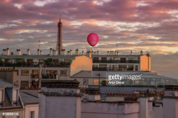 red helium balloon flying above paris during sunset with eiffel tower. - etalement urbain photos et images de collection