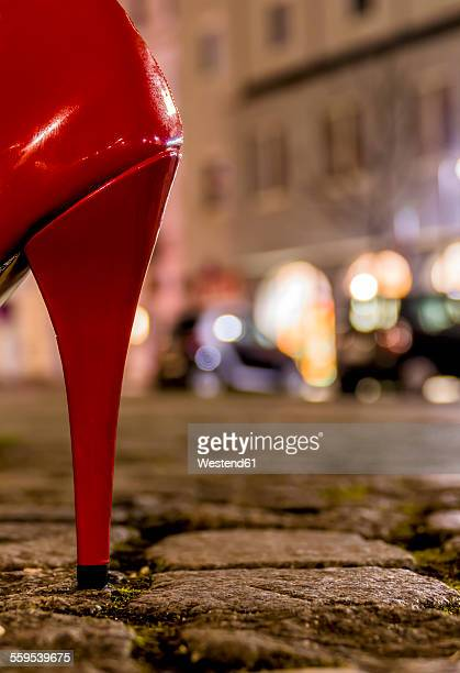 Red high heel on cobblestone street at night