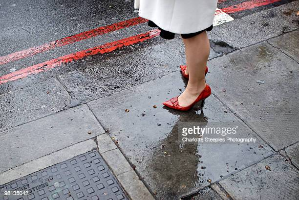Red high heeled shoes on wet pavement