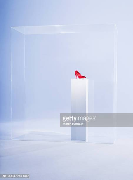 Red high heels on pedestal in glass cabinet