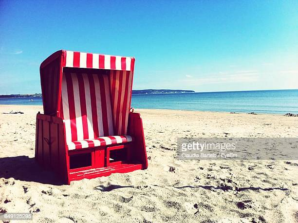 Red Hooded Chair At Beach Against Blue Sky On Sunny Day