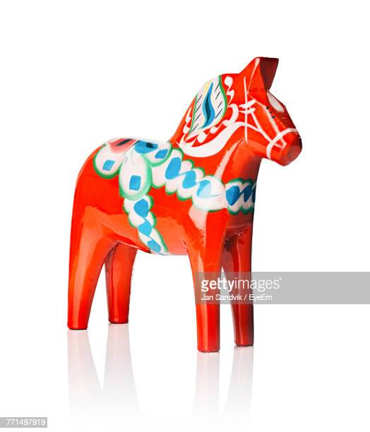 Red Horse Figurine Against White Background