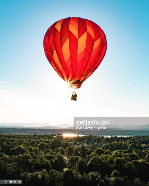 red hot air balloon flying over landscape against clear sky - hot air balloon stock pictures, royalty-free photos & images