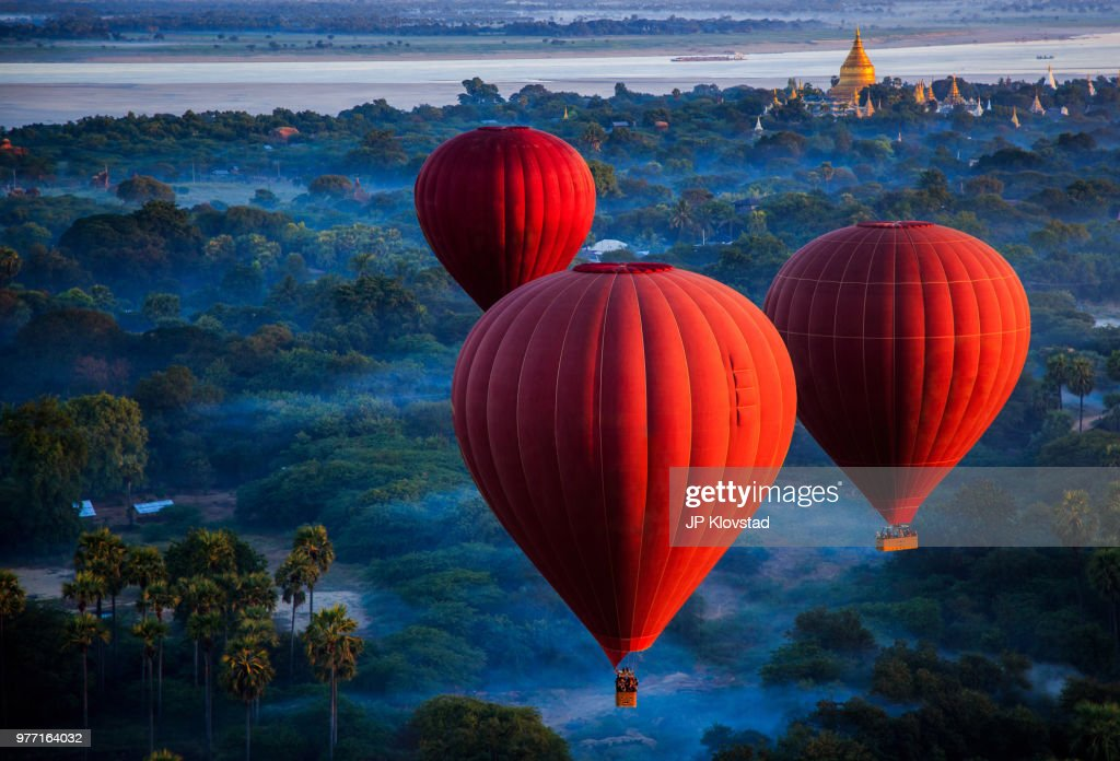 Red hot air balloons over jungle, Nyaung-U, Mandalay Region, Myanmar : Stock Photo