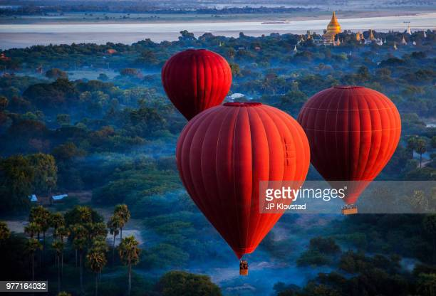 red hot air balloons over jungle, nyaung-u, mandalay region, myanmar - images stock pictures, royalty-free photos & images