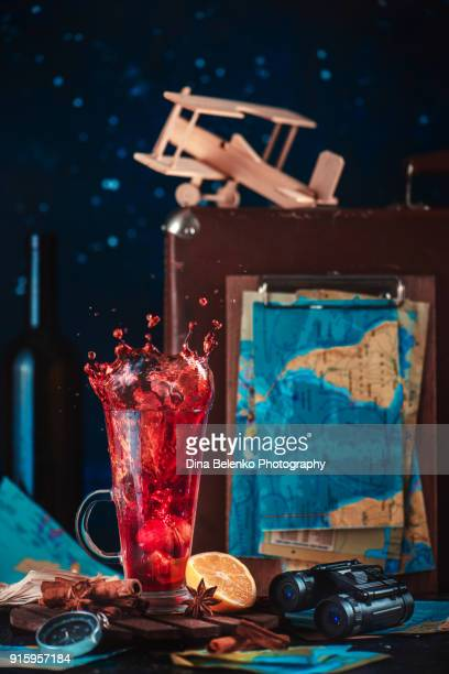 Red hot beverage with lemon and cinnamon in a tall glass. Travelling concept with a suitcase, wooden airplane model and binoculars.
